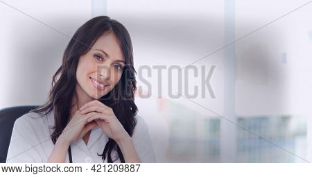 Composition of smiling female doctor in lab coat with stethoscope with vignette. global medicine professional and healthcare services concept digitally generated image.