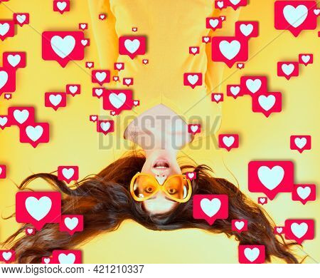 Joyful excited surprised young woman with flying hair and big funny glasses upside down gets likes in social media, success in social networks. Beautiful and funny young woman blogger