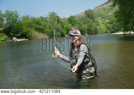young woman fly fishing in summer in large river
