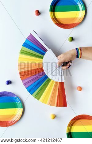 Lgbtq Community Pride Month Rainbow Concept Flat Lay. Hand With Ribbon Holds. Rainbow Fan. Paper Pla