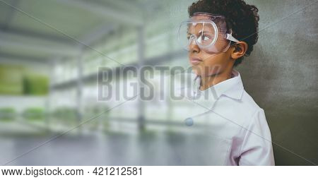 Composition of schoolboy with protective glasses in school laboratory with blurred classroom. science, learning and knowledge concept digitally generated image.