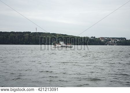 Excursion Ship On The Lake In The Center Of A City. White Yacht With People In The Middle Of A Large