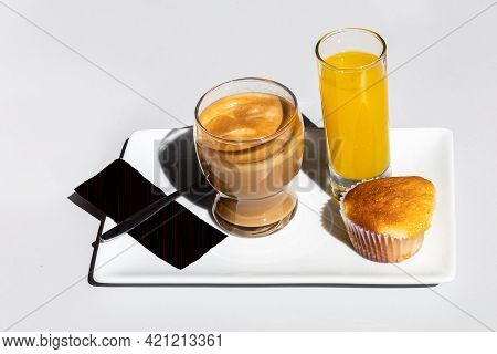 Continental Breakfast With Coffee In A Glass With Orange Juice And A Pastry Muffin On A Tray With Wh