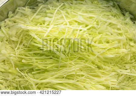 Fresh cabbage finely shredded in a bowl.