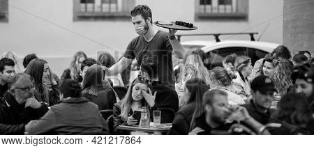 Strasbourg, France - May 19, 2021: Waiter With Ashtrays For People Eating Drinking At The Terrace Of