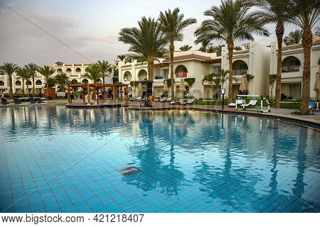 Egypt, Sharm El Sheikh, May, 2021 - Swimming Pool With The Some Beach Lounges With A View On Green P