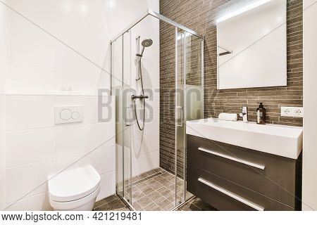 Contemporary Interior Design Of Bathroom With Glass Shower Cabin And Stylish Cabinet With Sink Near