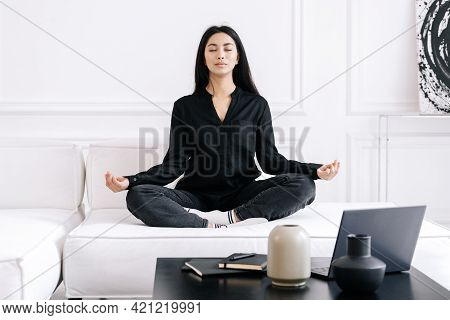 Young Asian Business Woman With Closed Eyes Meditating On Sofa At Home During Work Break, Doing Stre