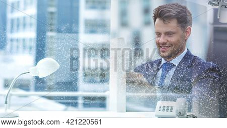Composition of smiling businessman in office over modern office building. global business and finance concept digitally generated image.