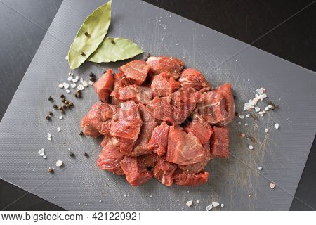 Raw Beef Of Veal Cut Into Cubes On A Gray Cutting Board Next To Bay Leaves, Black Pepper Peas And Co