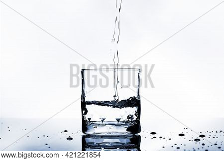 Pouring Purified Fresh Drinking Water And Bubbles Into Transparent Glass And Droplets On Selection F