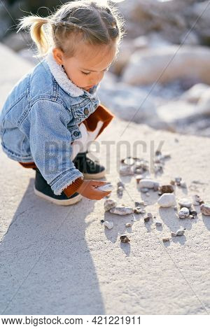 Little Pensive Girl In A Dress And A Denim Jacket Squatted On A Large Stone And Holds A Sea Pebble I