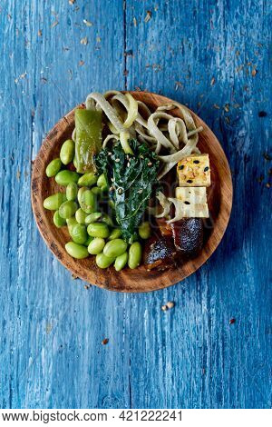 high angle view of a wooden plate with some spelt tagliatelle, kale, edamame beans, diced tofu and shiitake mushrooms, on a blue rustic wooden table