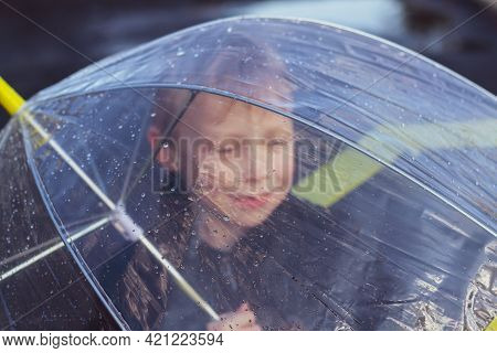 Caucasian Boy 6 Years Old Walks In The Rain In Spring Or Autumn Under A Transparent Umbrella.