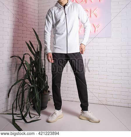 A Guy In A Tracksuit Against A White Brick Wall