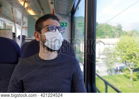 Travel Safely On Public Transport. Young Man Wearing Surgical Mask Looking Through Train Window. Tra