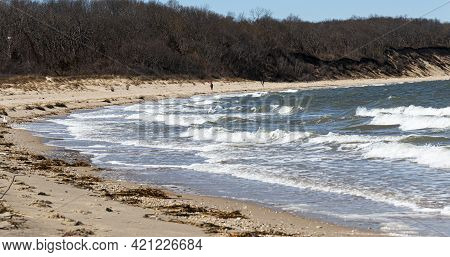 Rough Water On A Windy Day On The Shoreline Of A Norrth Shore Beach With Trees And Bluffs Sones And
