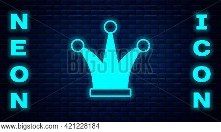 Glowing Neon Joker Playing Card Icon Isolated On Brick Wall Background. Jester Hat With Bells. Casin
