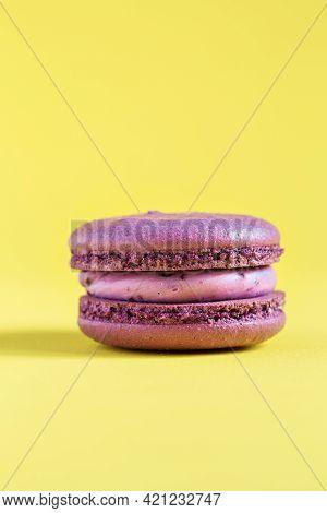 Purple Cake Macaron Or Macaroon On Yellow Background.