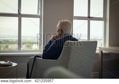 Rear view of senior man sitting on armchair and looking through the window. Lonely old man sitting at home near window during covid19 outbreak. Thoughtful retired man abandoned at nursing home.