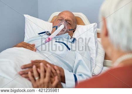 Lovely senior woman visiting her husband lying in hospital bed after postoperative. Aged wife holding hand and talking to sick man with oxygen mask resting on bed after surgery in private clinic.