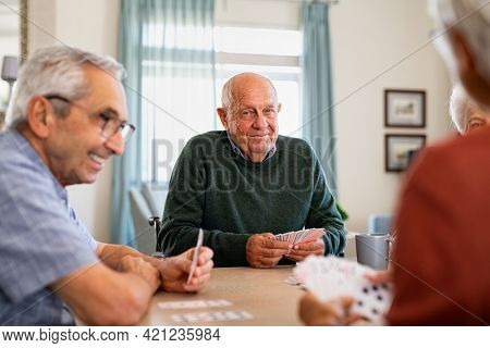Retired senior man in wheelchair playing cards with friends at nursing home. Smiling group of old people playing cards at care centre. Happy seniors playing at lunch table and having fun together.