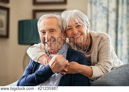 Portrait of romantic senior man with his beautiful wife stay at home. Smiling and caring old woman embracing from behind her retired husband sitting on couch. Cheerful old couple looking at camera.