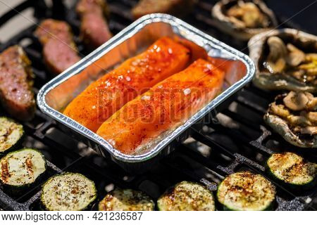 veal meat, salmon and zucchini on garden grill with charcoal