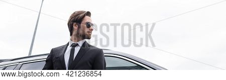 Low Angle View Of Bearded Bodyguard In Sunglasses And Suit Standing Near Modern Car, Banner.