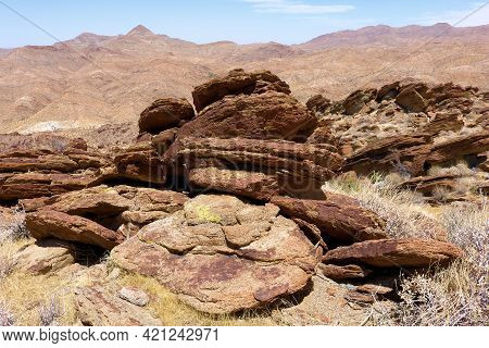 Rocks And Boulders On A Mountain Ridge Overlooking Arid Badlands At The Rural Colorado Desert In The