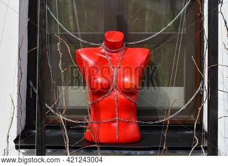 Red Mannequin With Bdsm Chains Stands On The Window.