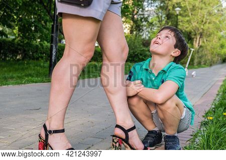 Boy Of Eight Sits On His Haunches At Feet Of His Mother And Looks Up At Her In Admiration. The Son I