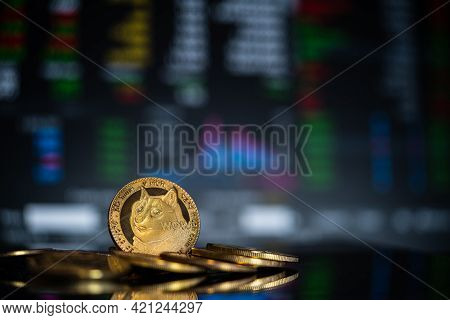 Focus Select And Blur Dogecoin Crypto Currency Silver Symbol And Stock Chart Candlestick On Tablets.