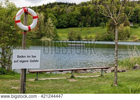 Lake Outdoor Pool With Swimming Platform In Green Landscape With Notice Sign In German, German Text