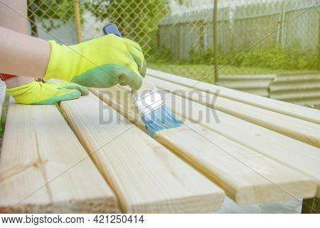 Woman With Brush Varnishes Old Wooden Boards. Worker Paint With Brush Wood Wall From Boards In Const