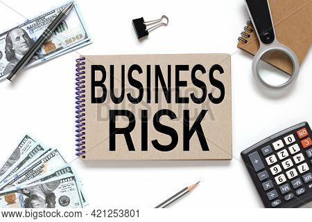 Business Risk. Business Concept. Notebook On White Workspace. Near The Notepad Dollar Bills And A Ca