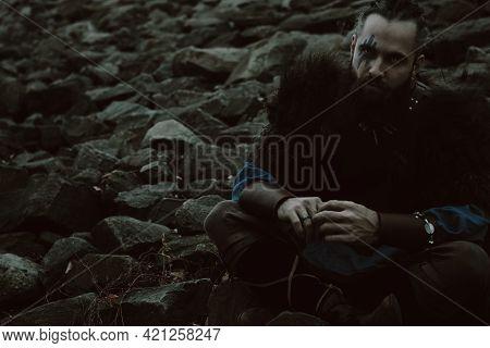 Brutal Scandinavian Young Warrior Sitting On Rocks