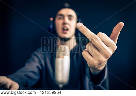 Streamer Show Gestures. Man Lose Game And Shows The Middle Finger. Guy With Headphones In Front Of A