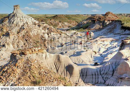 Unidentifiable Tourists Explore Dinosaur Provincial Park In Alberta, Canada, A Unesco World Heritage