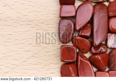 Red Jasper Heap Jewel Stones Texture On Half Light Varnished Wood Background. Place For Text.