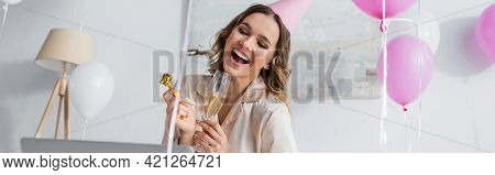 Positive Woman With Party Blower And Champagne Having Video Chat On Laptop At Home, Banner.
