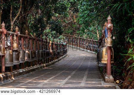 Walkway With The Metal Bronze Bells Around And Beside Of It In The Jungle Environment, At Wat Phra T