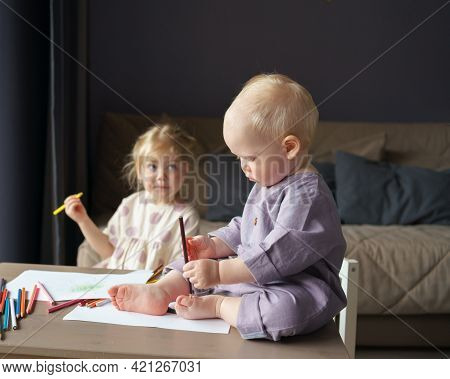 Cute Baby Boy With Golden Hair Sitting On Table, Playing With Colorful Pencils While His Older Siste