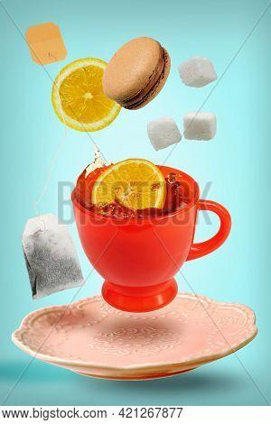 Levitating Orange Teacup With Flying Teabag, Lemon Slices And Sugar Cubes