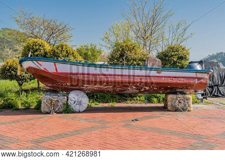 Small Fishing Boat With Outboard Engine Dry Docked On Large Foam Blocks.