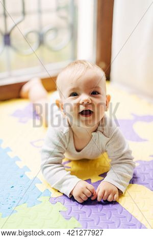 Surprised Joyful Baby Lies On His Tummy On A Colored Rug On The Floor Against The Background Of A Wi