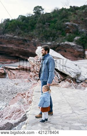Dad In A Denim Suit Holds The Hand Of A Little Girl In A Dress And A Denim Jacket While Standing On