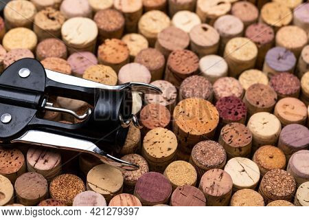 Close-up shot of various used wine corks stack and a corkscrew
