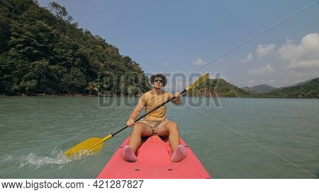 Man With Sunglasses And Hat Rows Pink Plastic Canoe Along Sea Against Green Hilly Islands With Wild