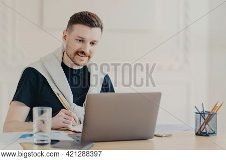 Smiling Young Man Freelancer In Earphones Writing Down Notes During Video Call With Collegues Or Onl